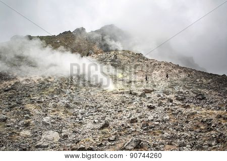 Berastagi, Indonesia - March 10, 2015: Tourists walking with a guide on Sibayak volcano near Berastagi in northern Sumatra, Indonesia