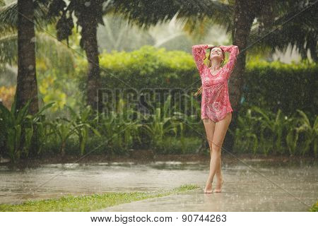 Beautiful woman under the tropical rain