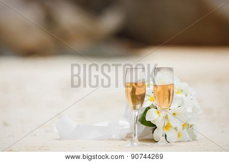Wedding bouquet of frangipani and flutes of champagne