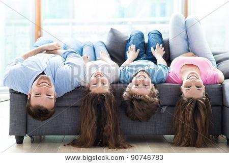 Family lying upside down on sofa