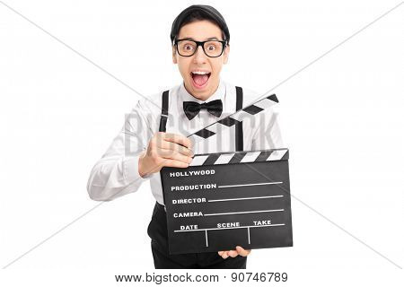 Excited movie director with glasses holding a movie clapperboard and looking at the camera isolated on white background