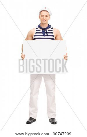 Full length portrait of a young handsome sailor holding a blank banner and looking at the camera isolated on white background