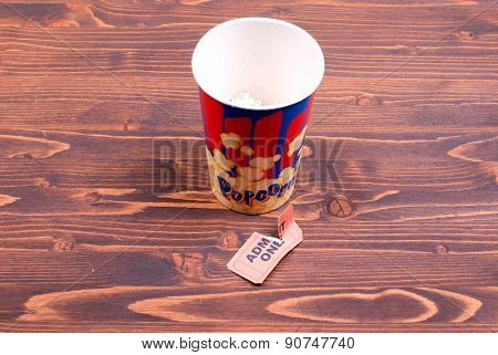 Half Cup Of Popcorn, Used Ticket On The Table Top View