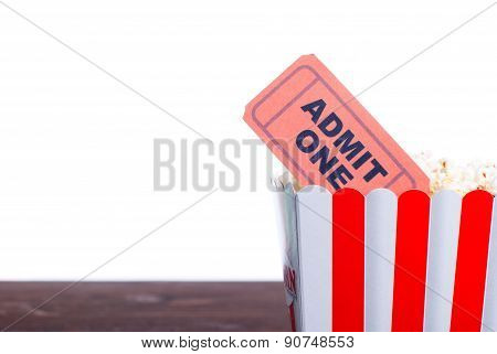 Ticket close-up in a box of popcorn stand on the board isolated background, side view, left space fo