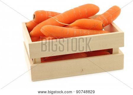 fresh carrots in and around a wooden box on a white background