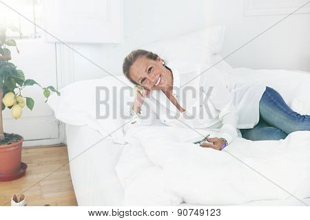 Senior Woman Reading In Bed A Tablet