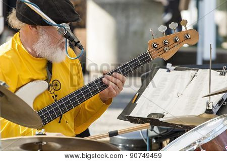 Old Male Musician Playing Guitar And Drums