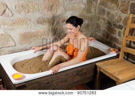 Woman in bath with clay
