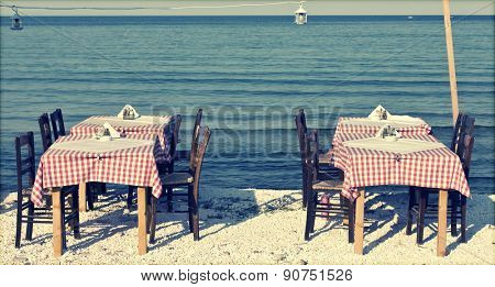 Dining table and chairs set outside on a beach - retro styled photo