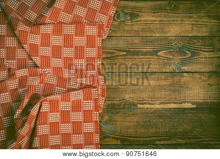 Wooden background with red checkered kitchen tablecloth
