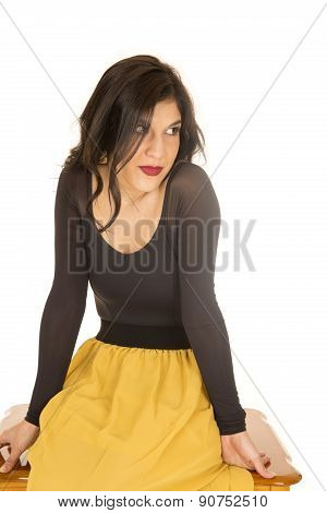 Female Model Sitting Wearing Black Top And Yellow Skirt