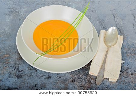 Pumpkin cream soup with spoon and napkin