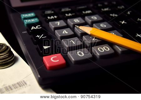 Pencil and Calculator beside the Bill and Coins