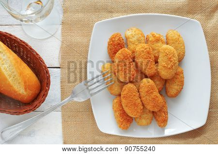 chicken nuggets served in a white bowl, top view
