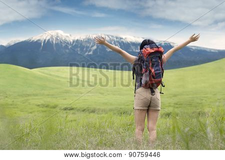 Backpacker Enjoying Fresh Air On Meadow