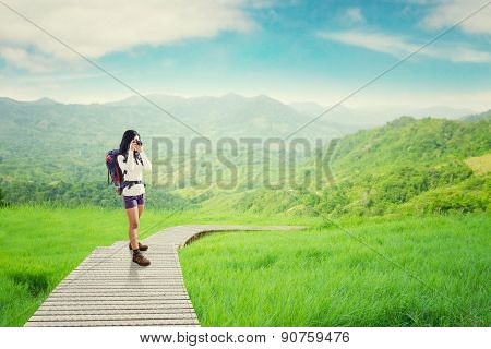 Backpacker Taking Picture On The Wooden Path