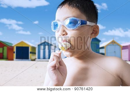 Naked Child Eating Ice Cream At Coast