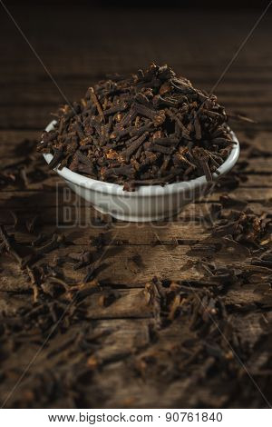 White teabowl with cloves scattered from it against wooden background