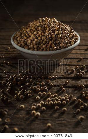 Coriander seeds against wooden background