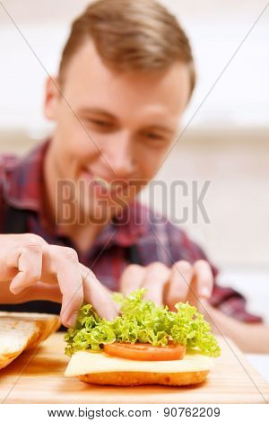 Close up of man decorating bread with lettuce
