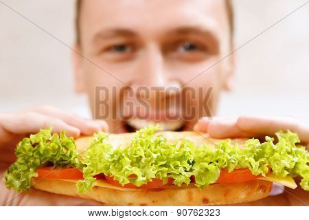 Close up of man taking bite sandwich