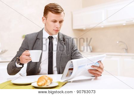 Businessman drinking with croissant coffee and reading newspaper