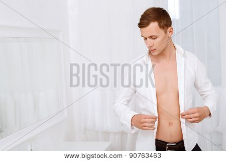 Handsome man holding shirt that he is wearing