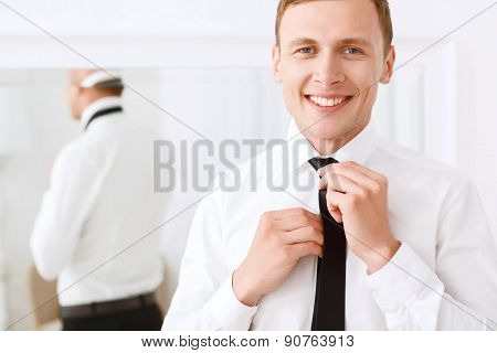 Smiling man fixing his tie