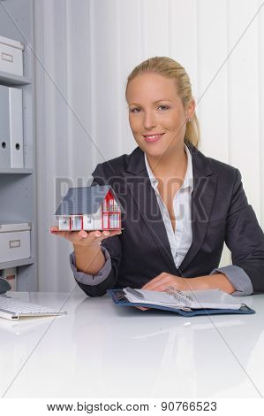 a young real estate agent with a model house in her office.