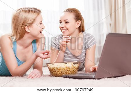 Two young girls eating popcorn