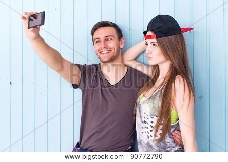 Couple friends taking selfie together wearing summer clothes  jeans shorts jeanswear street urban ca