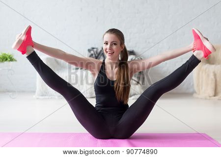 Funny smiling girl holding legs apart doing exercises aerobics warming up with gymnastics for flexib