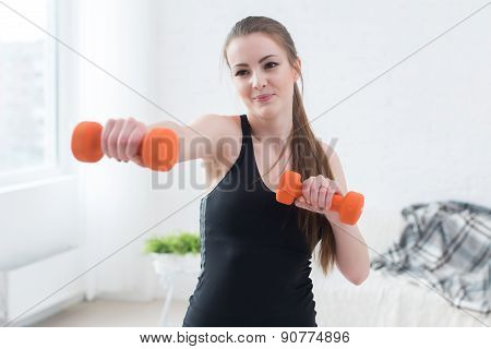 Active sportive athletic woman boxing dumbbells pumping up muscles towards camera in bright room con