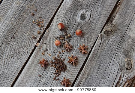 Carnation, Fragrant Pepper, Wood Nut And Anise Asterisks On A Wooden Table