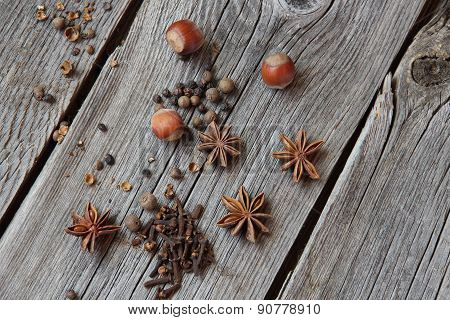 Wood Nut, Carnation, Fragrant Pepper And Anise Asterisks On A Wooden Table