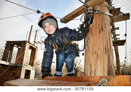 Smiling Boy Sits On Suspension Bridge And Looking Away