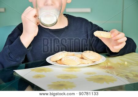 Little Boy Drinking Milk, Sitting At The Dinner Table. Biscuits On The Table And A Glass Of Milk.  H