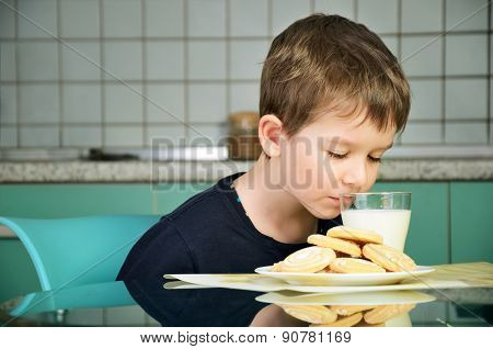 Cheerful Little Boy Sniffs With Pleasure Milk, Sitting At The Dinner Table. Horizontal