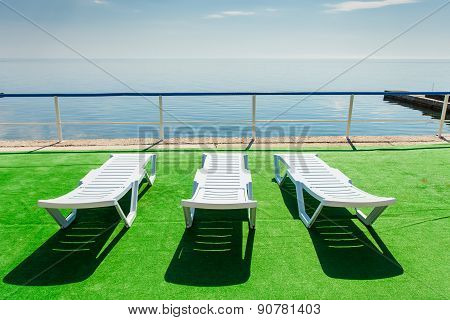 Three Deckchairs On Beach, Facing Out To Sea