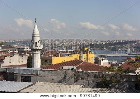 The minaret of a mosque Samani Virani and the Golden Horn metro bridge. Istanbul. Turkey.
