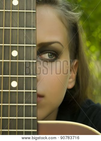 Portrait Of A Beautiful Girl Covering Her Eye With A Guitar