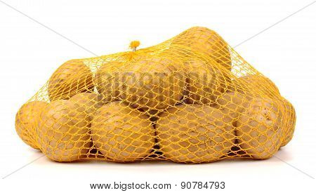 Heap Of Yellow Raw Potatos In Red String Bag.