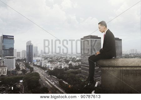 Business Man Sitting On Rooftop