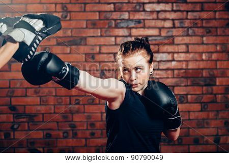 Woman wearing boxing gloves hitting training mits man is holding