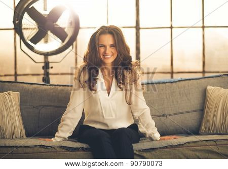 Smiling, Elegant Woman Leaning Forward Sitting On Sofa In Loft