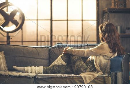 Woman In Casual Clothing Sitting On Sofa Looking Out