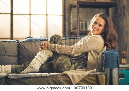 Casually Dressed Woman Sitting On Sofa Smiling