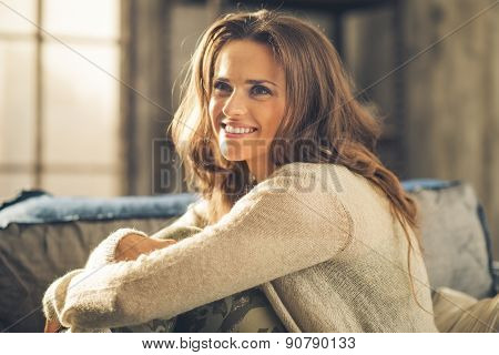 Smiling Woman Looking Up, Hugging Her Knees On Sofa