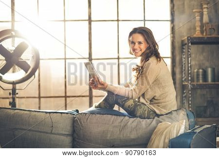 Smiling Woman Sitting On Back Of Sofa Looking Up From Table Pc