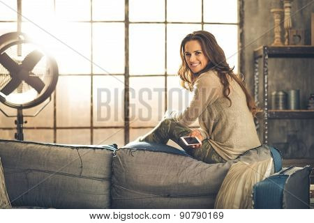 Smiling Woman Looking Over Shoulder Sitting On Sofa Back